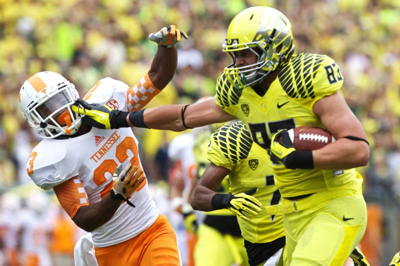 by: TRIBUNE PHOTOL JAIME VALDEZ - Oregon tight end Johnny Mundt keeps a Tennessee defender at bay as he runs after a catch in the Ducks' victory over the Volunteers Saturday afternoon at Autzen Stadium.