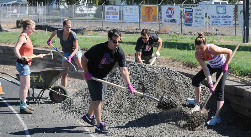by: LON AUSTIN - Nike employees spread gravel around the outer edge of the track at Ward Rhoden Stadium. This project was one of three Nike completed for the Crook County schools last week.