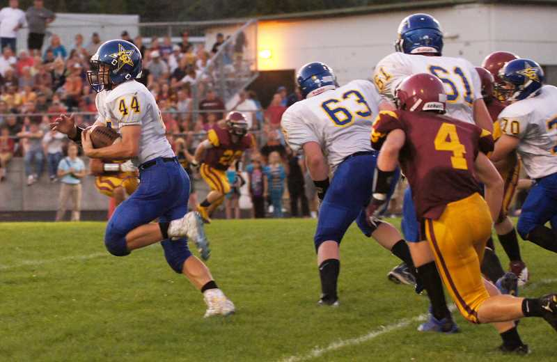 by: PHOTO COURTESY OF DOUG SMITH - Clark Woodward breaks into the open during the first quarter of the Cowboys loss to The Dalles-Wahtonka Eagle-Indians. Woodward finished with 40 yards in 10 carries as the Cowboys fell 45-28.