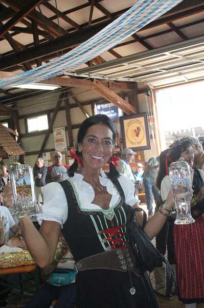 by: JEFF MCDONALD  - A woman celebrates wearing traditional garb Friday at Mount Angel's 48th annual Oktoberfest.