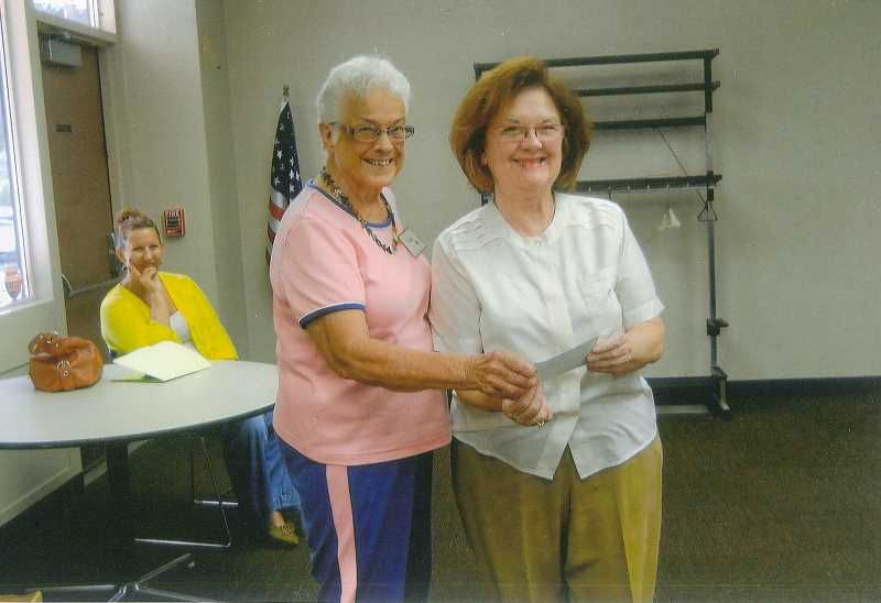 by: VI CUTLER - Vi Cutler of the Woodburn Garden Club presents a $250 check to Patricia Hyatt, who represents the Knot Garden Society.