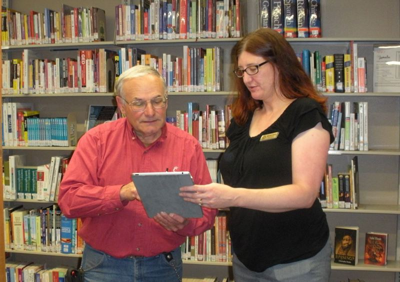 by: POST PHOTO: JIM HART - Monica Smith, childrens and reference librarian, assists Sandy area resident and library patron Dan Beltrami with the use of an electronic tablet. Library staff members are planning a class to help people learn to use various electronic devices.