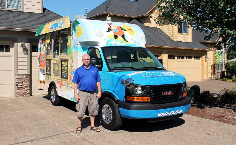 by: CORY MIMMS - Mark Burk in front of his Kona Ice truck, the first one based in Oregon. He and his wife, Lisa, operate the truck.
