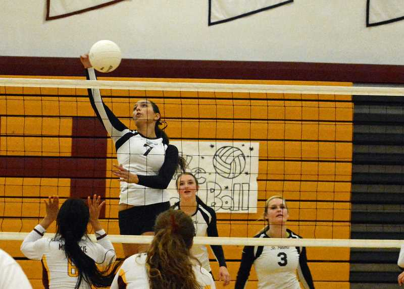 by: JOHN WILLIAM HOWARD - Senior Gabby Susee taps the ball over the net in the third set. Susee continued her strong showing this season in the win over Milwaukie, the Lions' second in a row.