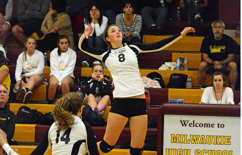 by: JOHN WILLIAM HOWARD - Junior Taylor Albertson leaps for the kill in the third set against Milwaukie. Albertson injured her left wrist late in the game.
