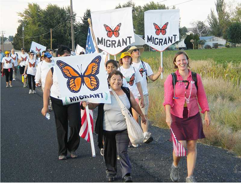 by: SUSAN MATHENY/MADRAS PIONEER - Marchers on the first leg of a three-day trek to Rep. Greg Walden's office in Bend display signs in support of immigration reform legislation. The monarch butterfly symbolizes the migration between Mexico and the U.S.