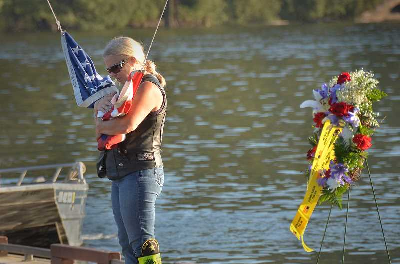 by: VERN UYETAKE - Lora Baker, a member of the Patriot Guard Riders from West Linn, clutches the American flag that was raised at the start of the 9/11 ceremony.