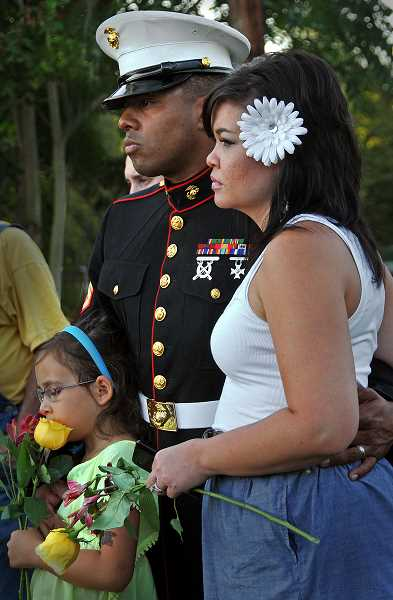 by:  VERN UYETAKE - Staff Sgt. Randy Cerda, his wife, Makananda, and daughter, Anisa, watch as the American flag is raised.