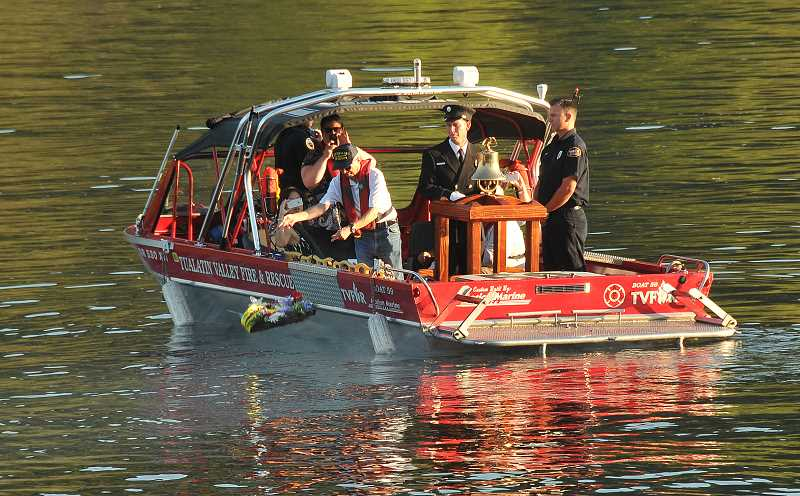 by:  VERN UYETAKE - Mayor John Kovash places the ceremonial floral wreath into the river.