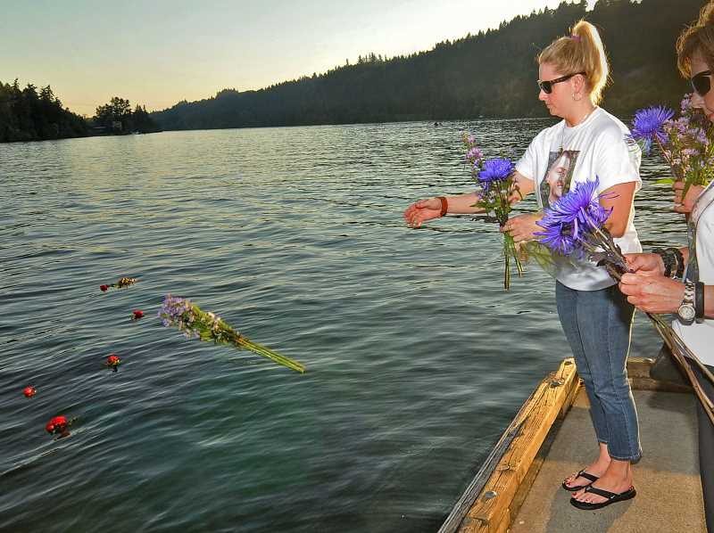 by:  VERN UYETAKE - Erin Percin Moffenbeier tosses her bouquet of flower into the water.