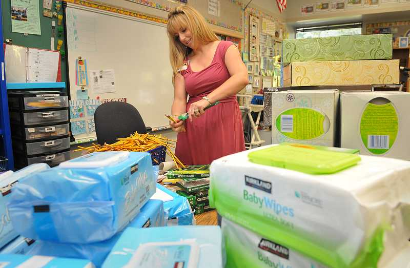by: REVIEW PHOTO: VERN UYETAKE - Rivergrove Elementary Schools Elona Schreiner sorts through supplies her fifth-grade class brought by recently.