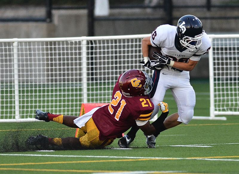 by: VERN UYETAKE - Lake Oswego receiver Daniel Dennis breaks a tackle en route to the end zone for what would be an 85-yard touchdown against Central Catholic last week.