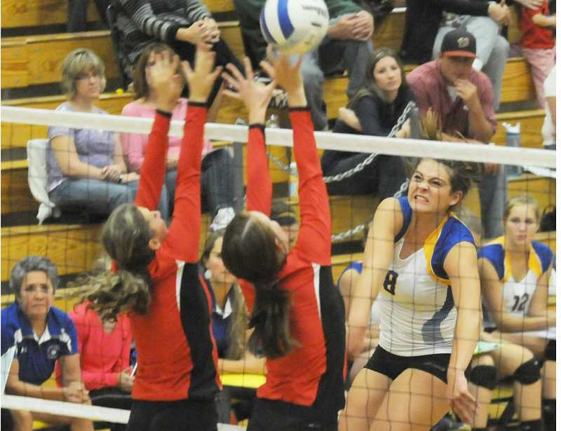 by: LON AUSTIN/CENTRAL OREGONIAN - Kathryn Kaonis pounds the ball over the block of two Mountain View Cougar defenders during the Cowgirls three-set victory over the Cougars. Kaonis finished the match with 11 kills in 22 attempts.