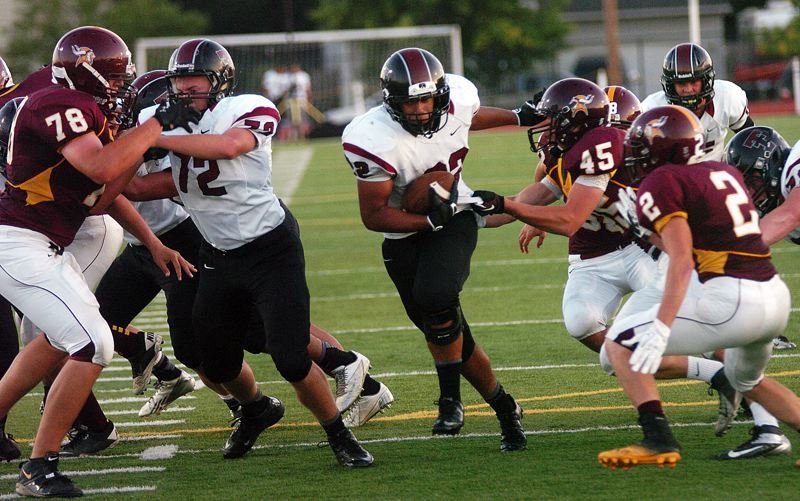 by: DAN BROOD - INTO THE CLEAR -- Tualatin junior running back Eli Robinson, behind the blocking of senior Brock Hulse (72), has a hole to run through in Friday's win over Forest Grove.