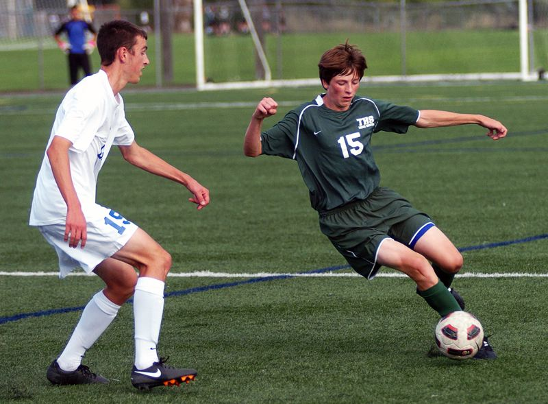 by: DAN BROOD - FOOTWORK -- Tigard High School junior Cam Van Sant (right) looks to make a move past a Grant player  during Tuesday's match held at Delta Park. The Generals scored a 5-2 victory.