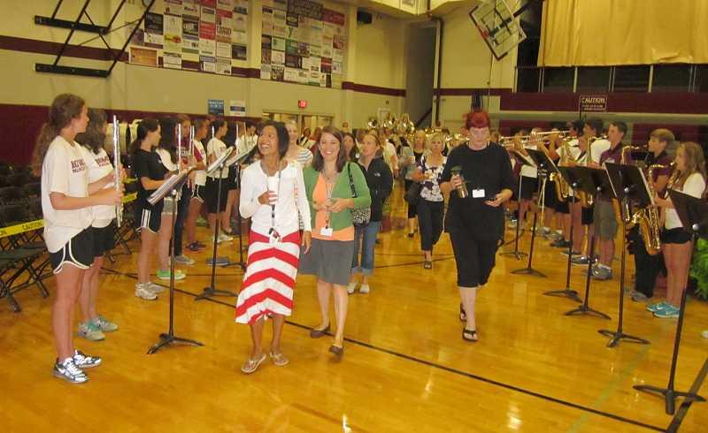 by: BARBARA SHERMAN - HEADING BACK - Sherwood School District staff members enter the Sherwood High School gymnasium for the annual Back to School rally Aug. 28 between rows of SHS band students belting out rousing music to kick off the event.
