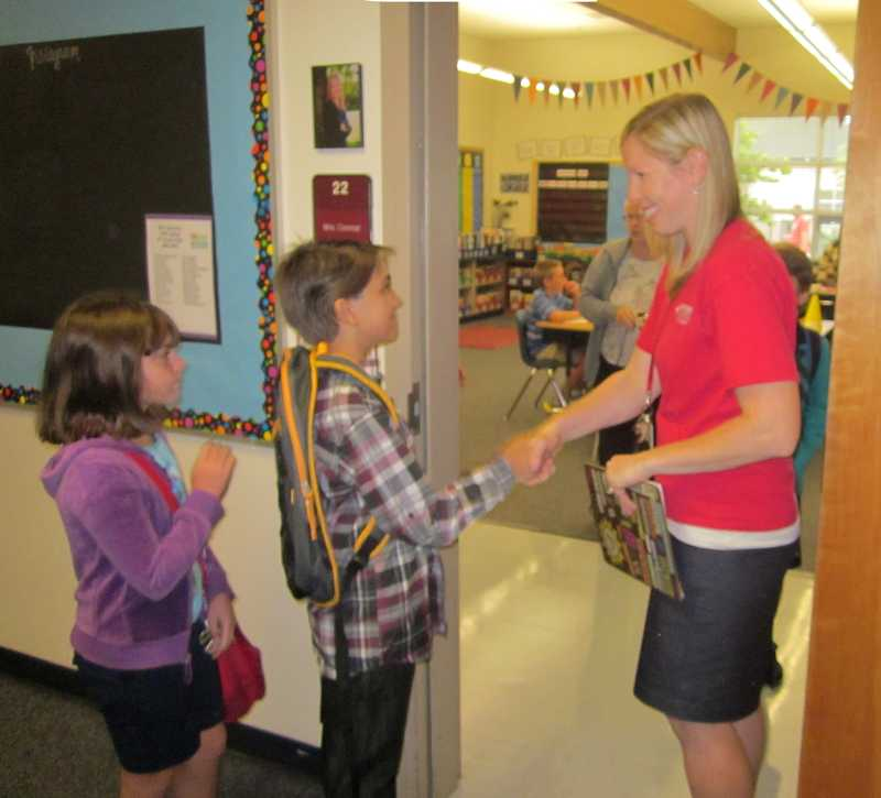 by: BARBARA SHERMAN - OFF TO A GOOD START - On the first day of school Sept. 3 at Hopkins Elementary, fifth-grade teacher Marika Conrad greets new student Jordan Junkin while Isla Cox waits her turn at the classroom door. Conrad is one of only nine winners across the nation to be given the 2013 Distinguished Teaching Award from the National Council on Geography Education.The Distinguished Teaching Award honors those who have made extraordinary contributions to the teaching and learning of geography in the classroom.