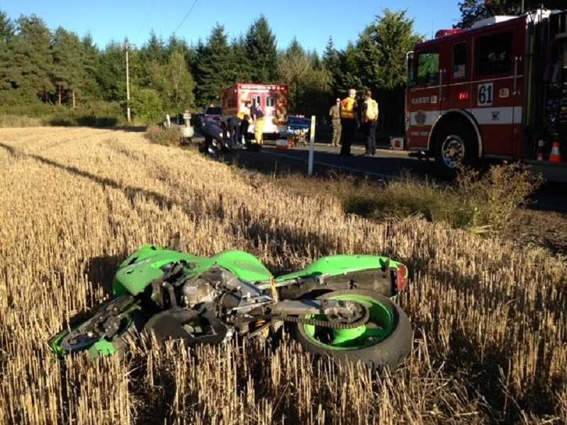 by: PEGGY SAVAGE - Canby paramedics work on an injured motorcyclist on Mulino Road Thursday evening