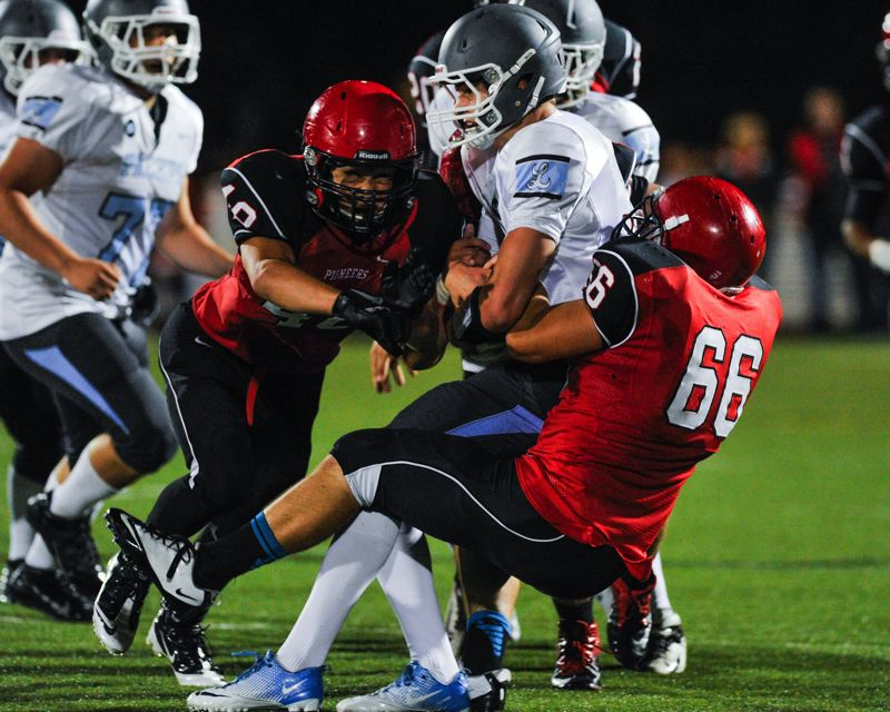 by: JOHN LARIVIERE - Oregon City defensive tackle D.J. Vandervort (66) teams up with Pioneer linebacker Jake Yoshimura to sack Lakeridge quarterback Eric Dungey in last Fridays showdown with the Pacers.