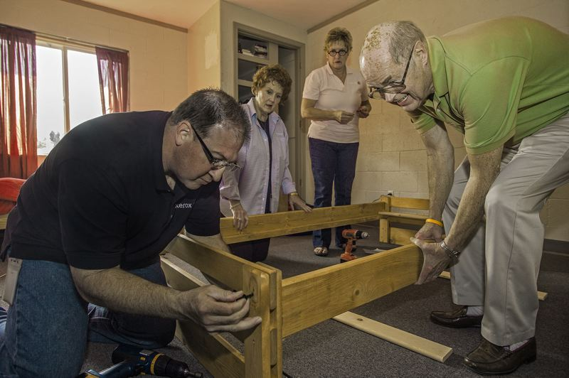 by: SPOKESMAN PHOTO: JOSH KULLA - Xerox employee Garry Jones, left and former Xerox employee Dick Spence, right, assemble a new bed for the Parrott Creek Ranch.