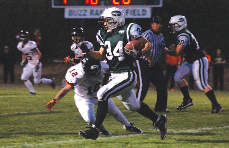 by: ESTACADA NEWS: PARKER LEE - Estacada running back Alex Barstad eludes a tackler in the backfield Friday against Yamhill-Carlton.