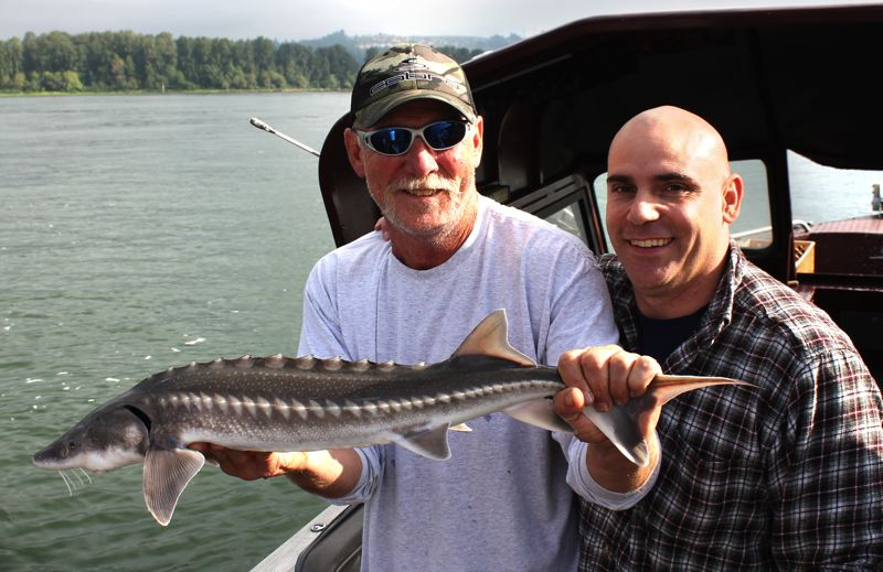by: OUTLOOK PHOTO: CARI HACHMANN - Don Schneider holds a juvenile sturgeon caught by his client, Bill Weatherbee, right, who lives on Mount Hood.