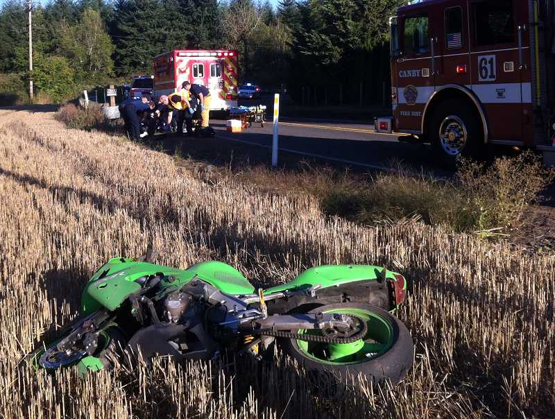 by: SUBMITTED PHOTO - While paramedics and fire personnel work to get Faron Michael Bennett ready for transport (background), the remains of his motorcycle sit in a wheat field along Mulino Road.