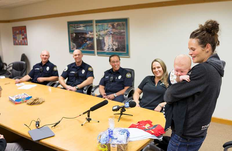 by: NEWS-TIMES PHOTO: CHASE ALLGOOD - Katie Marquess of Beaverton (far right) holds 1-month-old Thor Jacob Hoffman as she chats with the 911 operator -- Forest Grove resident Lisa Peterson (second from right) and paramedics who helped her through the babys birth on Sept. 7.
