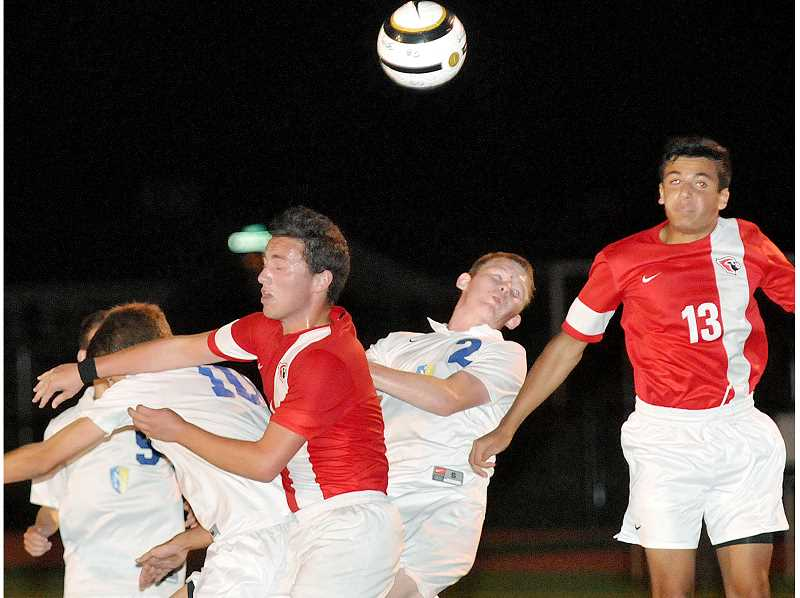 by: SETH GORDON - Head for the game - Several Newberg and Lincoln players attempt to get their heads on the end of a cross into the Cardinals' penalty box in the second half of the Tigers' 2-0 home loss on Thursday. Newberg had a goal called back for a foul and was denied a penalty kick as it rallied to get back in the game in the second half.