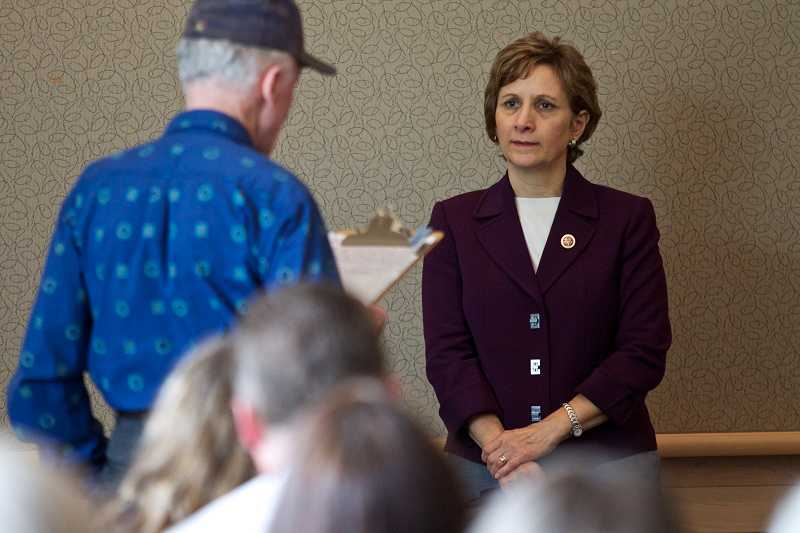by: TIMES PHOTO:JAIME VALDEZ - U.S. Rep. Suzanne Bonamici listens as constituent Ralph Robins voices his concerns about Syria during a town hall meeting in the Tualatin Public Library Community Room.