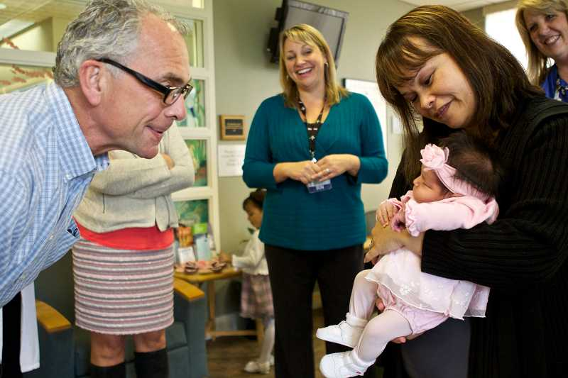 by: TIMES PHOTO: JAIME VALDEZ - Tualatin Mayor Lou Ogden introduces himself to baby Arianni Moreno and her mom, Sophia. Arianna was recognized as the 100th baby born in Tualatin during the citys Centennial year.