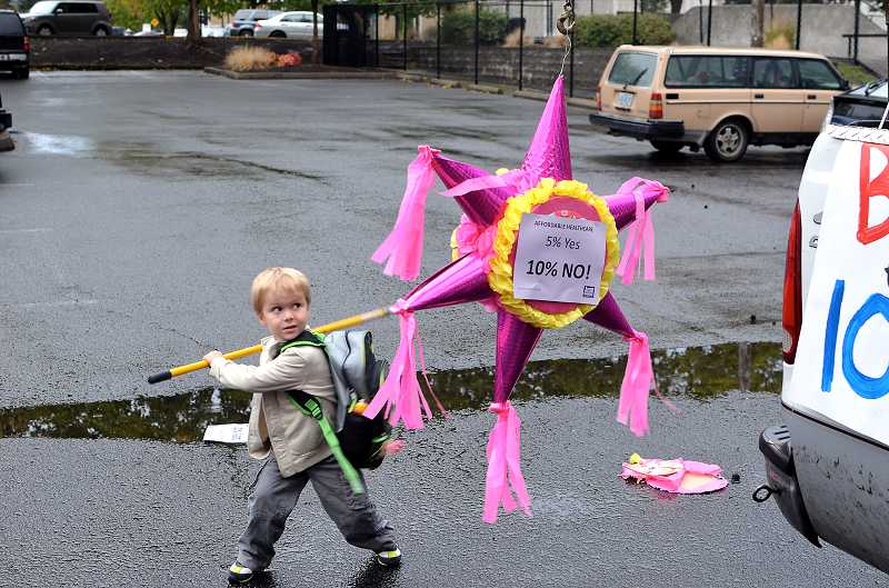 by: TIMES PHOTO: GEOFF PURSINGER - Evan Polivka, 5, takes aim at a pinata during the Faire for a fair contract rally outside of city hall. The fun and games were meant to show city officials that contract negotiations impact whole families, not just city workers.