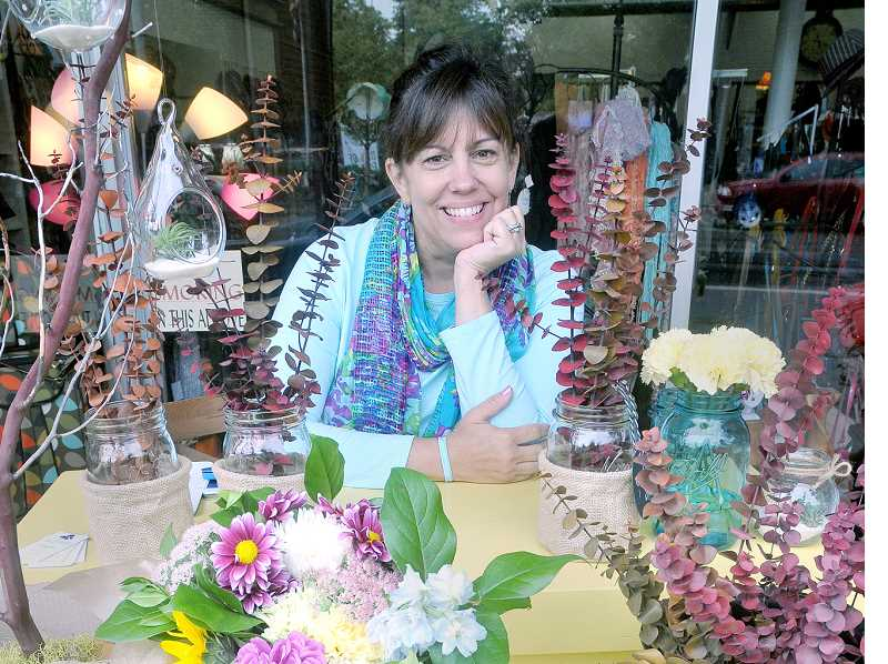 by: GARY ALLEN - Coming up roses -- Suzanne Meadows started her flower cart,  'The Blue Poppy,' out of a passion for flowers and a desire to provide fresh flowers for Yamhill County. Her cart can be found outside Janis Jewelry and Gifts every Saturday.