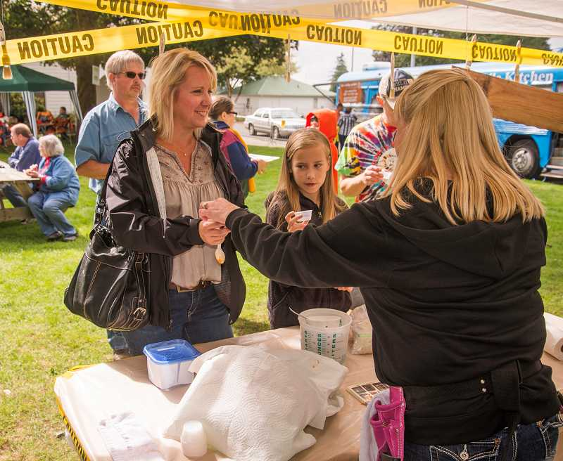 by: RAY HUGHEY - Customers sample the chili offerings at the Netter Construction booth at the Chili Cookoff.