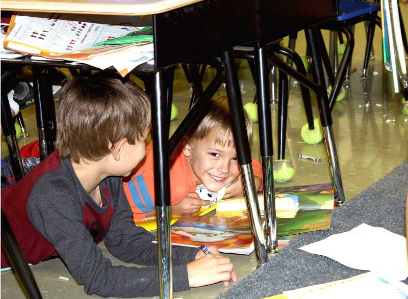 by: PEGGY SAVAGE - Two little first graders huddled under their desks with their books during silent reading time in Blackman's classroom Friday.