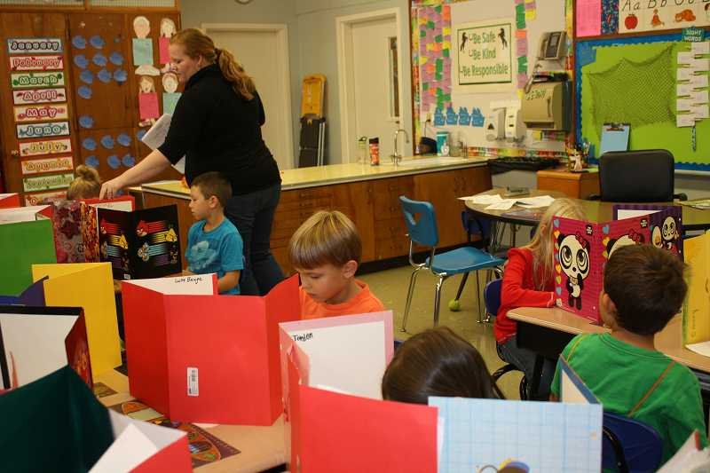 by: PEGGY SAVAGE - Blackman has the first graders set up 'offices' out of folders while answering questions on a math assessment test.