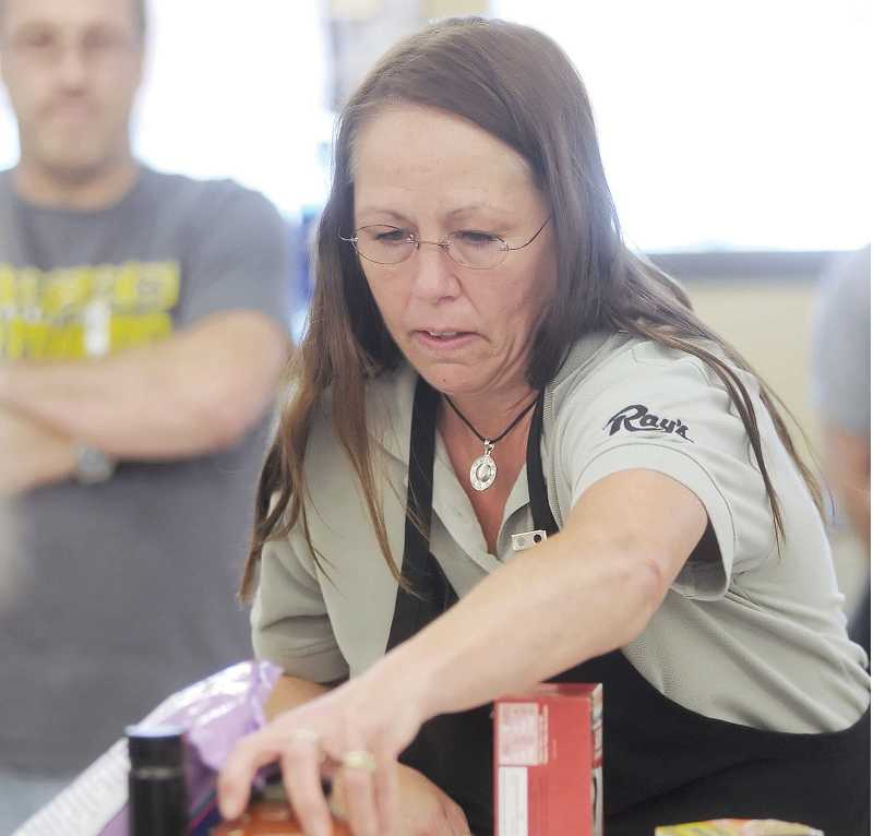 by: CONTRIBUTED PHOTO - Janese Clark focuses on her mission during a grocery-bagging competition held at Ray's Food Place in Central Point earlier this month.
