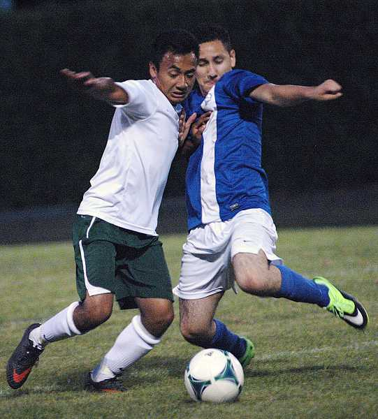 by: PHOTO BY PARKER LEE/PAMPLIN MEDIA GROUP - Madras sophomore Gustavo Pacheco (blue jersey) challenges an Estacada player for the ball in the White Buffalos' 2-0 win against the Rangers on Thursday in Estacada.