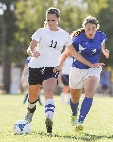 by: NEWS-TIMES PHOTO: AMANDA MILES - Banks junior midfielder Emily Vandehey (11) eludes a Valley Catholic defender during last Thursday's girls soccer match.