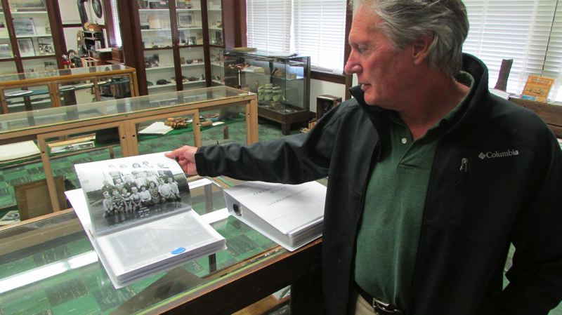 by: DARRYL SWAN - Courthouse Historic Museum curator Les Watters flips through a binder of historic class photos on display. The schools exhibit is a current effort to catalog the rich history of Columbia County's schools.