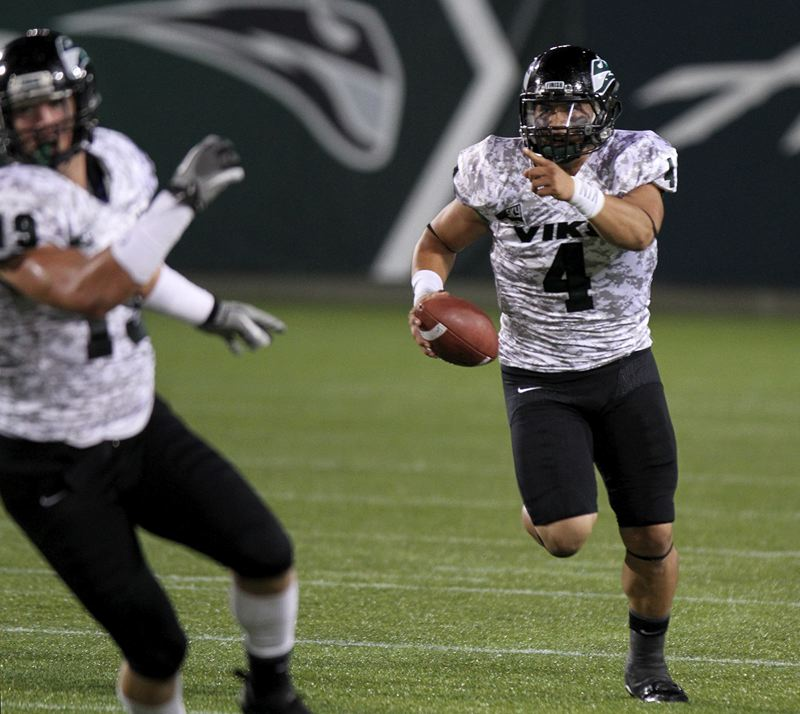 by: TRIBUNE PHOTO: JONATHAN HOUSE - Quarterback Kieran McDonagh of Portland State directs his blockers on a run against Cal Poly.