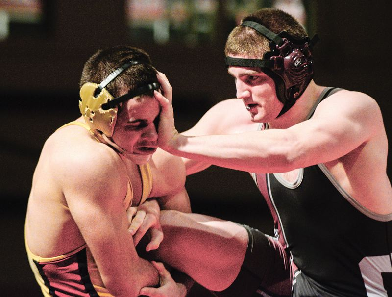by: HILLSBORO TRIBUNE PHOTO: CHASE ALLGOOD - Before heading off to Linfield College and joining the Wildcats football team, police cadet Michael Schrader (right) was a star wrestler at Glencoe High School. In February, Schrader won the district title and qualified for the state tournament.