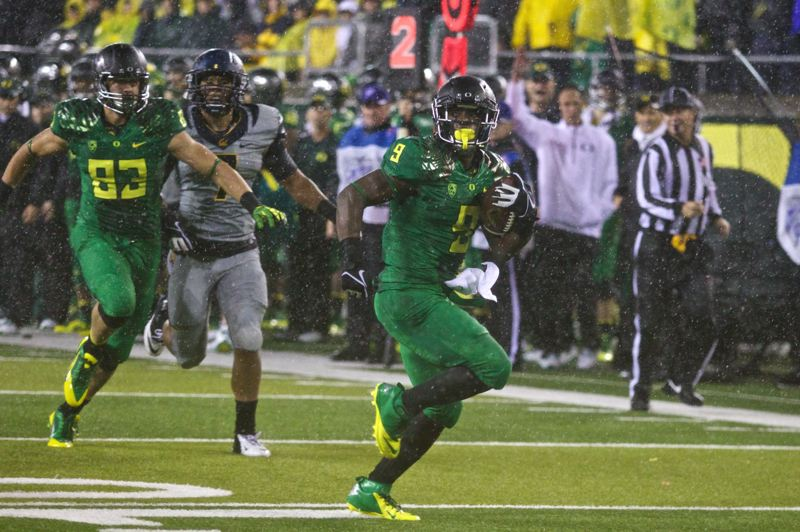 by: TRIBUNE PHOTO: JAIME VALDEZ - Byron Marshall runs for an Oregon Ducks touchdown in the rain at Autzen Stadium.