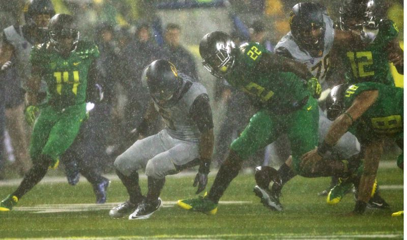 by: TRIBUNE PHOTO: JAIME VALDEZ - Oregon Ducks defenders Ifo Ekpre-Olomu (14) Derrick Malone (22) Rodney Hardrick (48) and Brian Jackson (12) dive for a loose ball by California running back Brendan Bigelow.