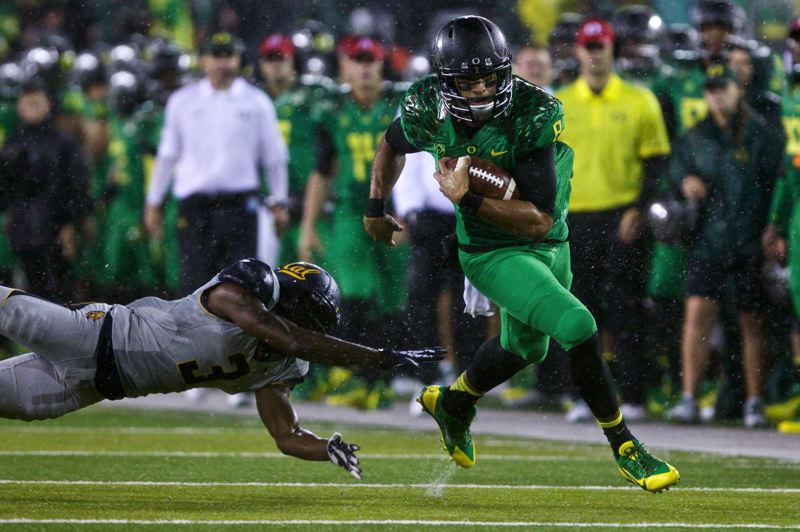 by: TRIBUNE PHOTO: JAIME VALDEZ - Oregon quarterback Marcus Mariota escapes the hands of Cal cornerback Kameron Jackson.