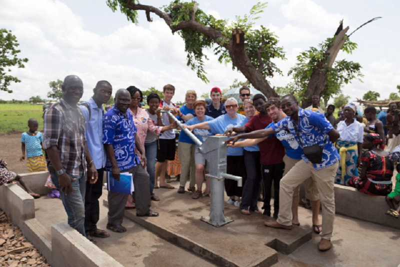 by: COURTESY OF LAURIE THIBERT - FRESH WATER ON TAP -- Mary Thibert (fifth from right) stands with the Water Access Now and CRS teams at the new water borehole in Adaribe village in Ghana's northern region.