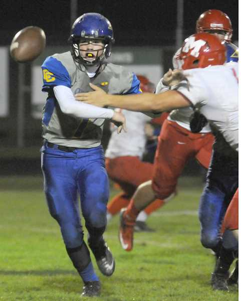 by: LON AUSTIN/CENTRAL OREGONIAN - Mike Irwin thows a pass to Cole Ovens. Irwin completed 8 of 11 passes during the Cowboys victory over the Madison Senators.