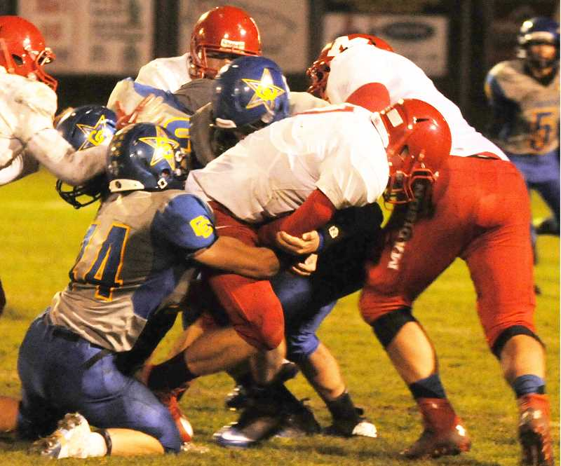 by: LON AUSTIN/CENTRAL OREGONIAN - Clark Woodward and Zach Smith tackle a Madison runner for a short gain during the Cowboys 49-0 victory over the Senators. Smith led the Cowboys in tackles with 12.