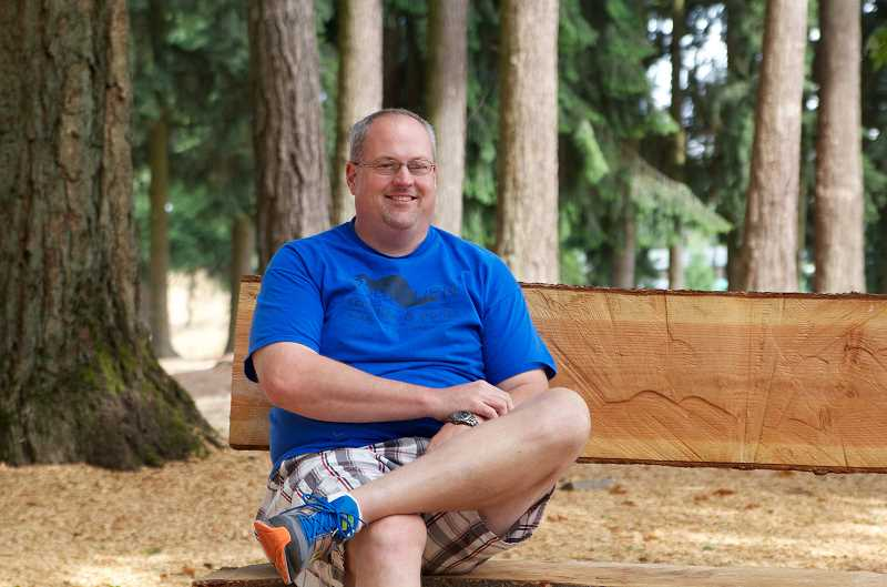 by: YG MEDIA  - Stu Spence, Woodburns recreation services manager who is sitting on a newly constructed log bench in Legion Park, was recently named the new professional of the year by Oregon Recreation & Park Association.