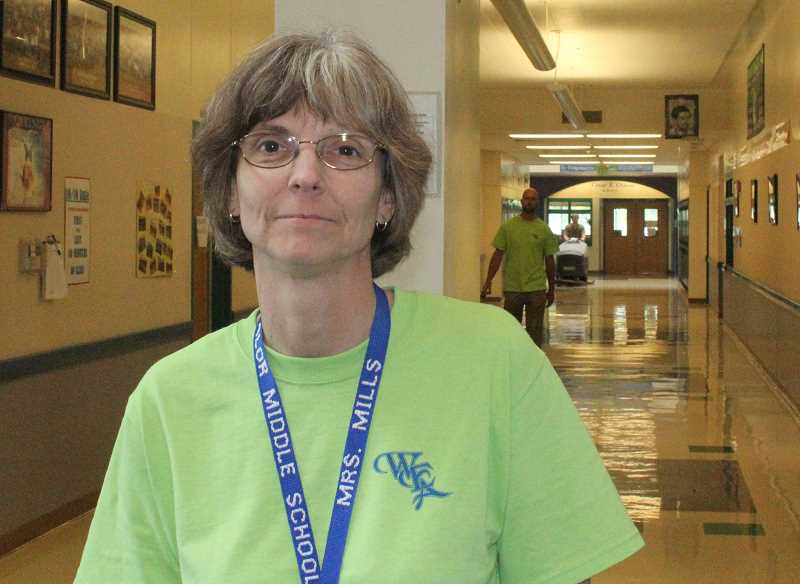 by: JEFF MCDONALD  - Cherene Mills, president of Woodburn Educators Association and teacher at Valor Middle School, wore light green Wednesday to stand up for teacher concerns in the district.